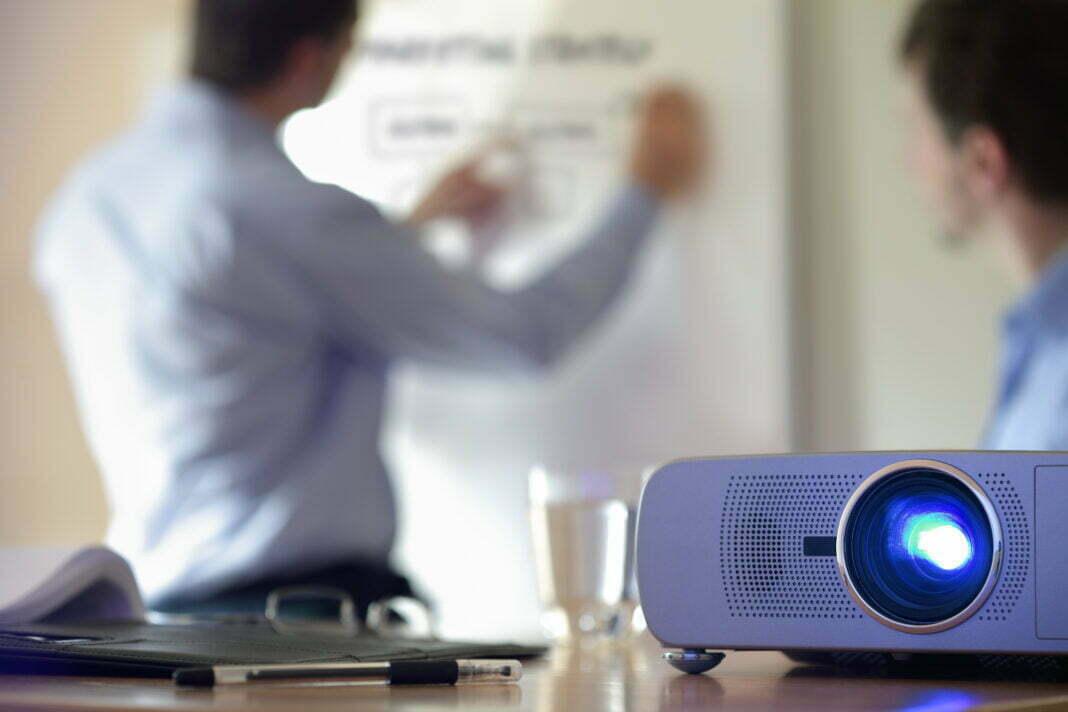 Projektor i forgrunden med en mand der tegner på whiteboard i baggrund
